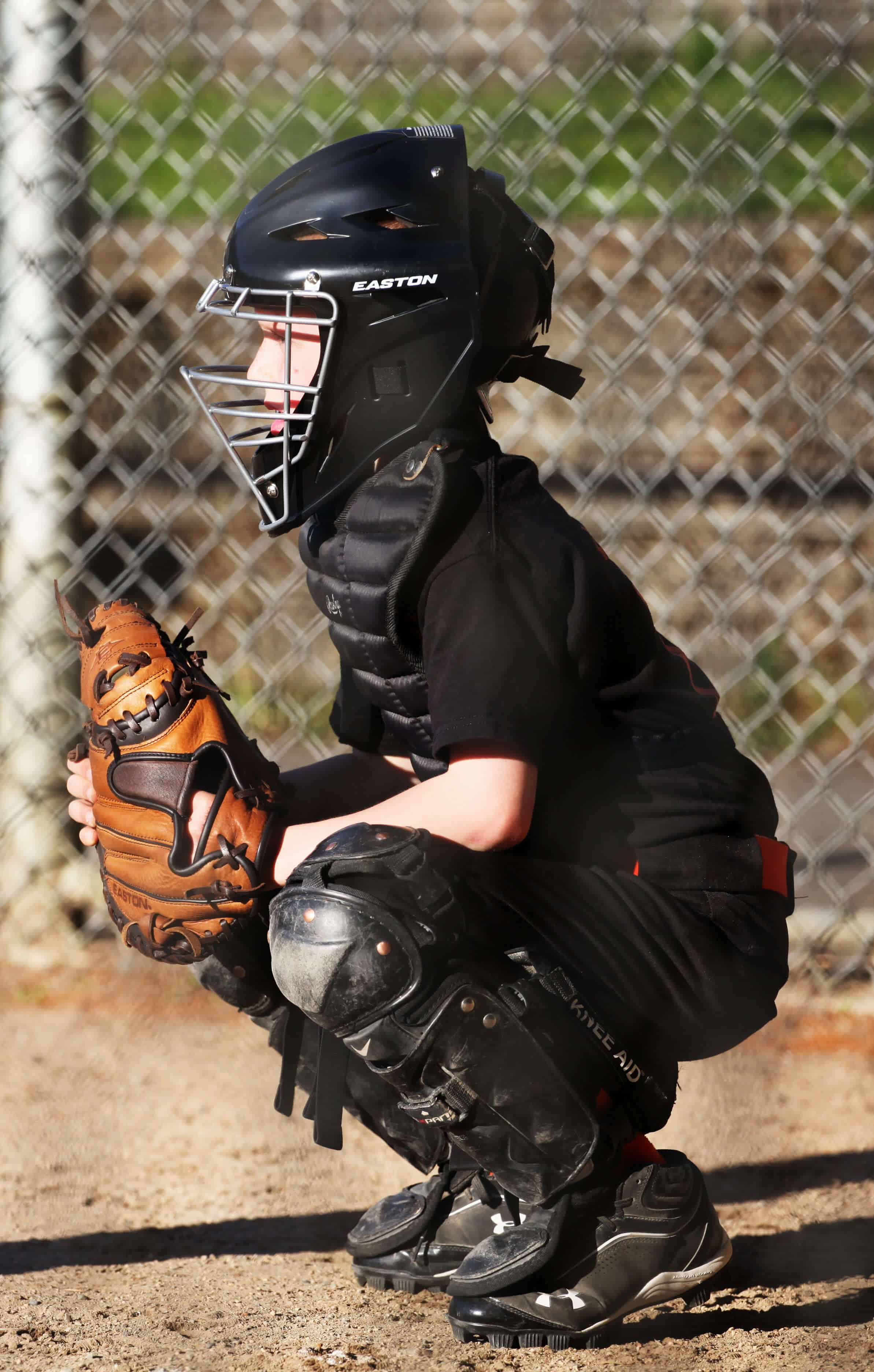 Youth Catcher in crouching position ready to catch the pitch