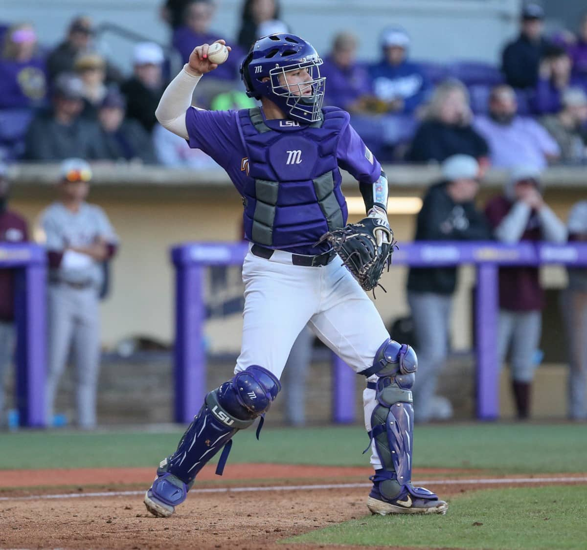 LSU catcher, catcher throwing to pitcher, marucci chest protector and leg guards, LSU catcher wearing Marucci catcher's gear